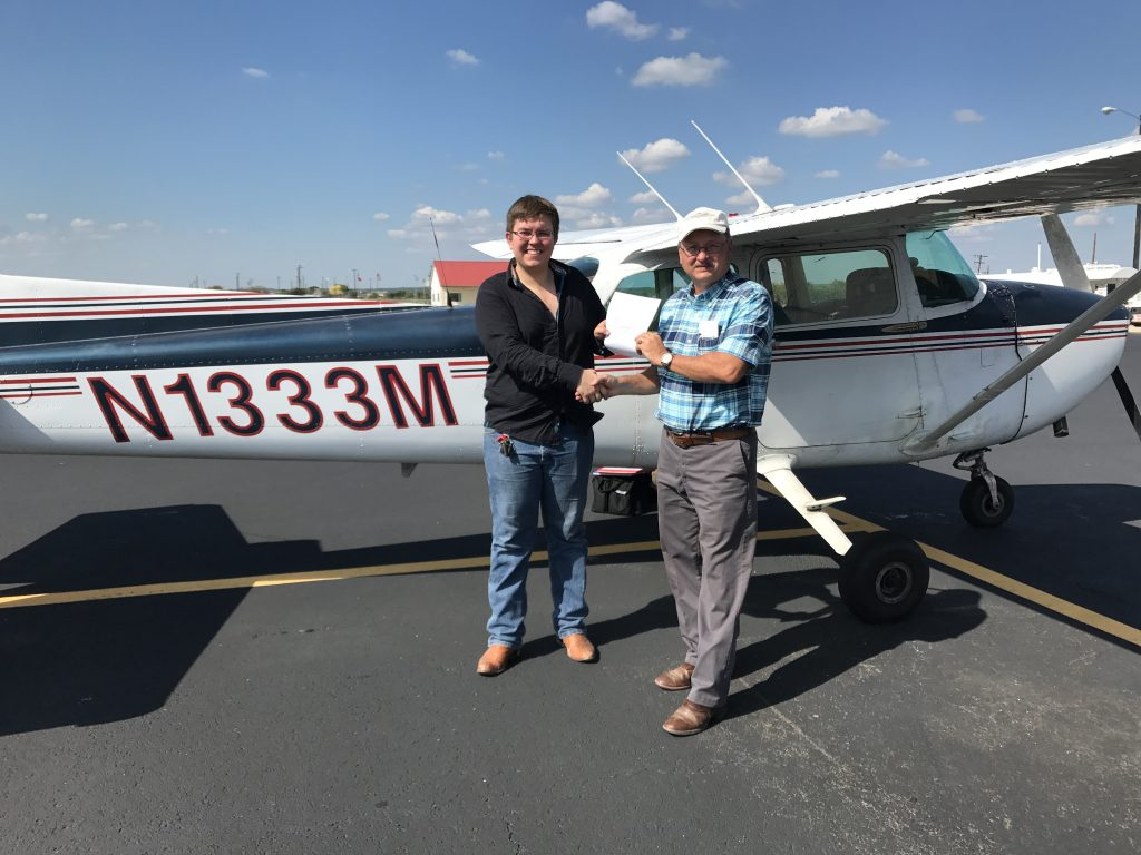 Two men (student and instructor) standing in front of a blue and white Cessna 172L arplane. The student has just earned his pilot license