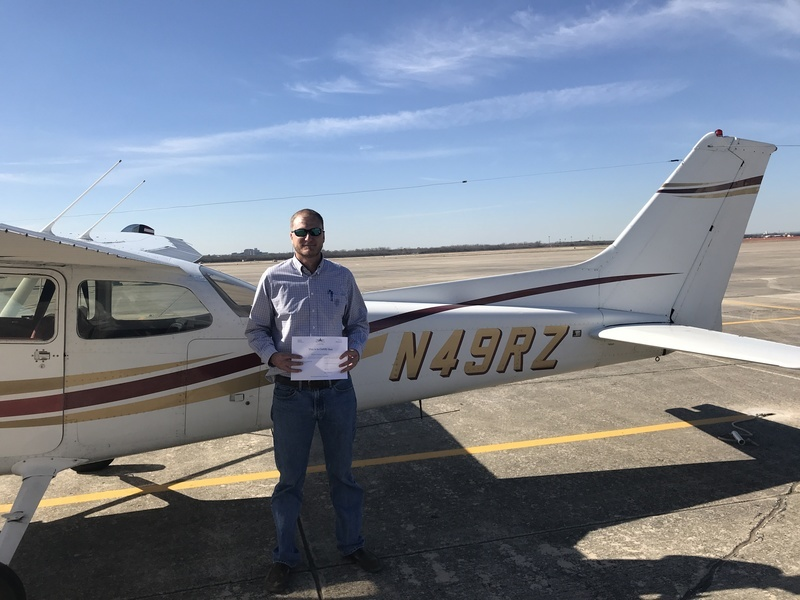 Man standing in front of a white Cessna 172 holding a paper pilot certificate