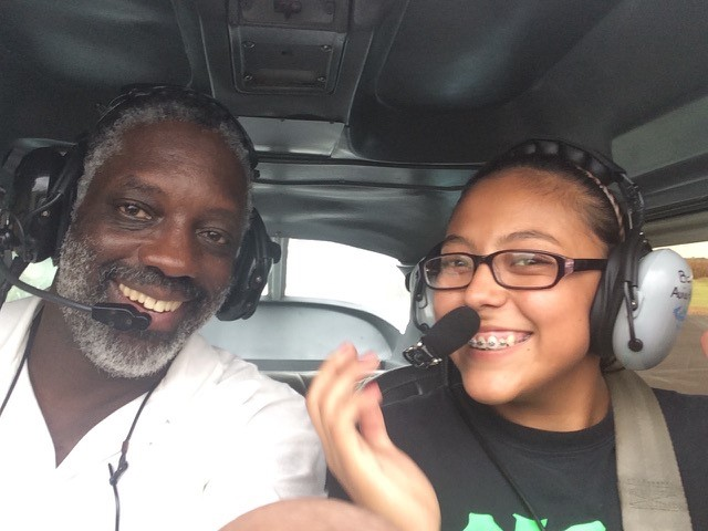 A man and young woman ride in small airplane