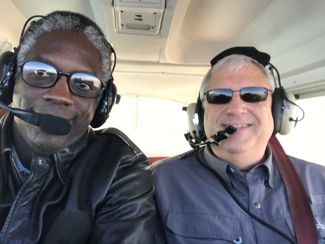 Two pilots sit in small plane, smiling